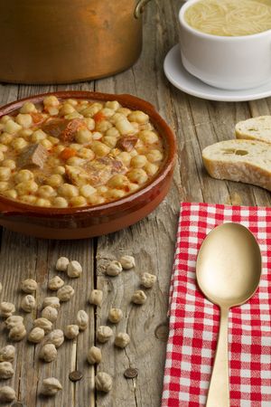 Spanish Cocido, soup in a white bowl, bread, golden spoon and old pot on a wooden table
