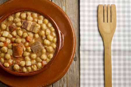 pot belly: Spanish Cocido in an earthenware pot and dish, and a wooden fork on a white and grey napkin