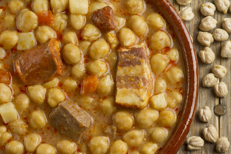 pot belly: Dried chickpeas and spanish Cocido in an earthenware pot on a wooden table Stock Photo