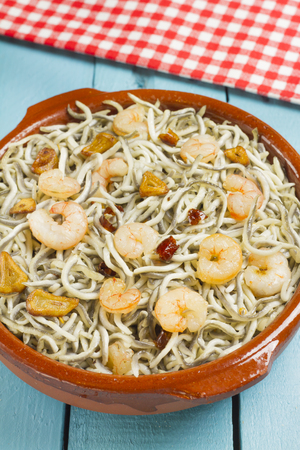 Surimi elvers with prawns, garlic and pepper in a traditional earthenware dish