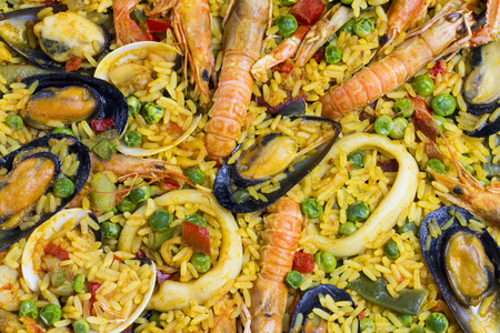 valencia orange: Close up to a spanish Paella, with mussels, shellfish, prawn, norway lobsters, rice and other ingredients