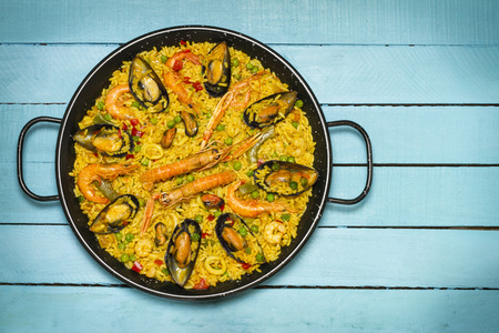 Spanish paella on a blue wooden table, copy space on the right