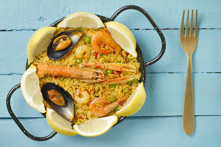 valencia orange: Spanish paella on a blue wooden table with fresh lemon and a golden fork