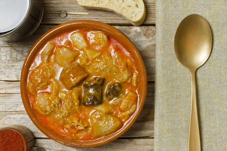 Spanish callos, bread, wine, paprika, napkin and golden spoon on a wooden table