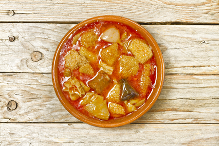 Spanish callos in an earthenware bowl on a wooden table Archivio Fotografico