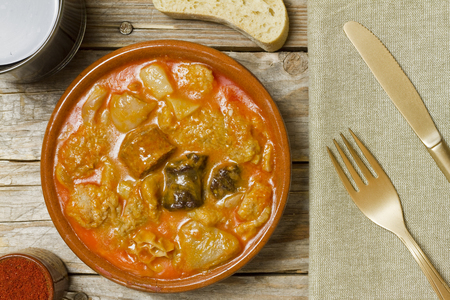 Spanish callos, bread, wine, paprika, napkin and golden fork and knife on a wooden table