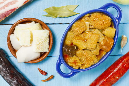 Spanish callos on a blue bowl and ingredients on a blue wooden table Archivio Fotografico