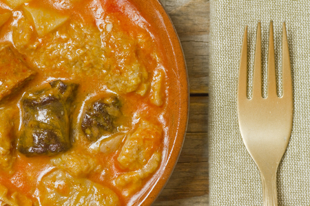 Spanish callos, napkin and golden fork on a wooden table Archivio Fotografico