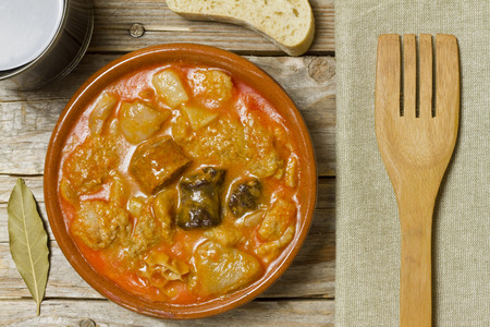 Spanish callos, wine, bread, bay leaf, napkin and wooden fork on a wooden table Archivio Fotografico