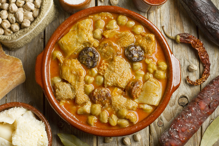 Spanish callos with chickpeas and ingredients on a wooden table