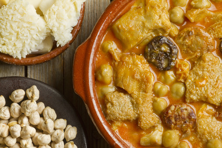 Close up of Spanish callos with chickpeas, with raw tripes and chickpeas on clay pots