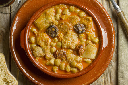 Spanish callos with chickpeas on an earthenware bowl and dish on a wooden table Archivio Fotografico