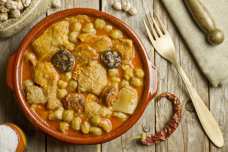 Spanish callos with chickpeas on a wooden table with golden fork Archivio Fotografico