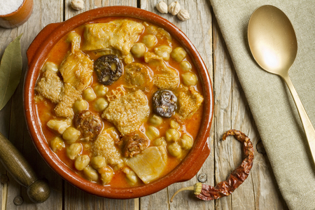 Spanish callos with chickpeas on a wooden table with golden spoon
