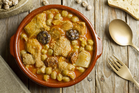 Spanish callos with chickpeas on a wooden table with golden spoon and fork