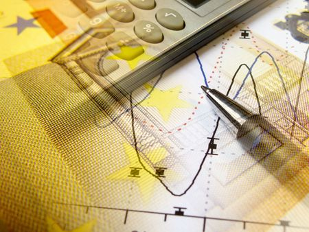 A pen and calculator with money against statistic chart - abstract business background.