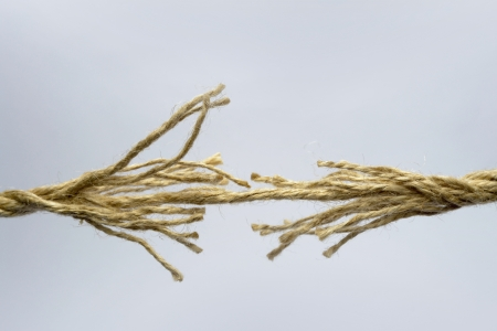Broken rope on grey background.