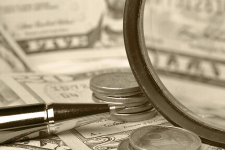 Business background with magnifier, coins and pen. Stock Photo - 13400703