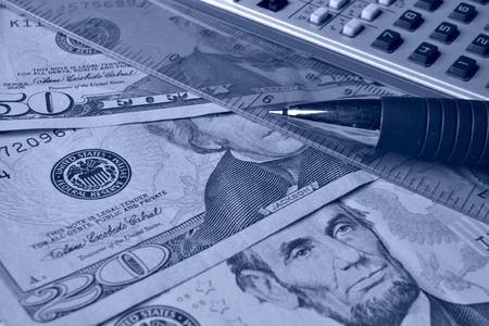 Business background in blues with money, ruler, calculator and pen. photo