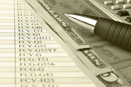 Business background with money, ruler, calculator and pen, in sepia. photo