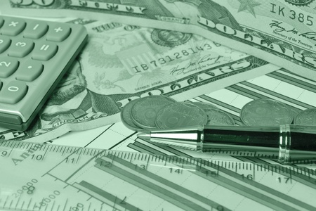 Business background with money, ruler, calculator and pen, in greens. photo
