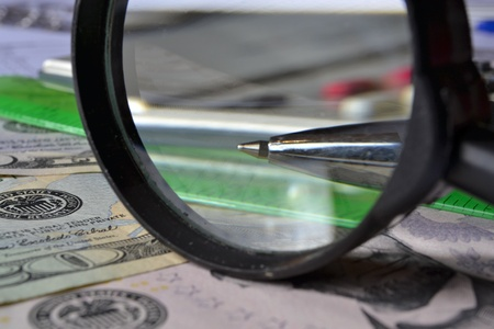 Business background with money, magnifier and pen. photo