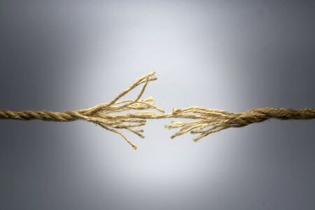 severance: Broken rope on dark background. Stock Photo