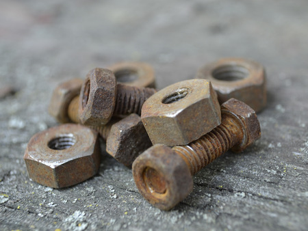 Rusty bolts and nuts on the wooden background.
