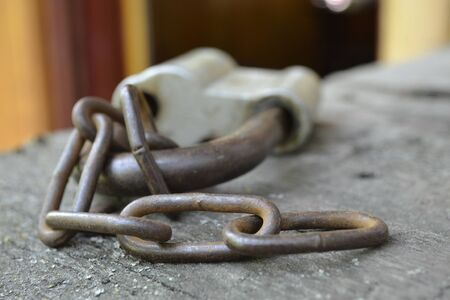 rusty chain: Rusty lock with chain on wooden background.