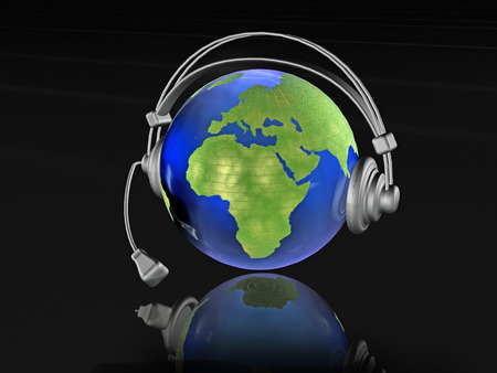 musik: Globe with headphones on the black background. Stock Photo