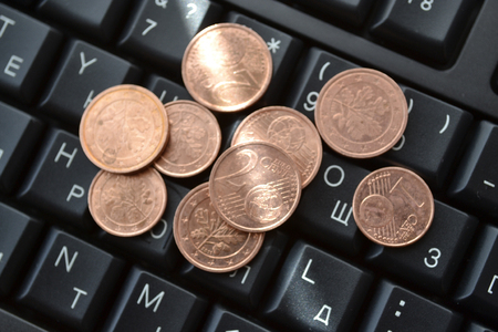 allegory: Coins on the keyboard - abstract business background.