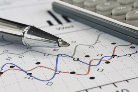 Business background with graph, pen and calculator. Stock Photo