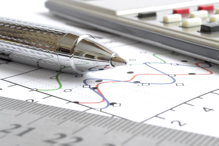 Calculadora, regla y gráfico de fondo empresarial. Foto de archivo
