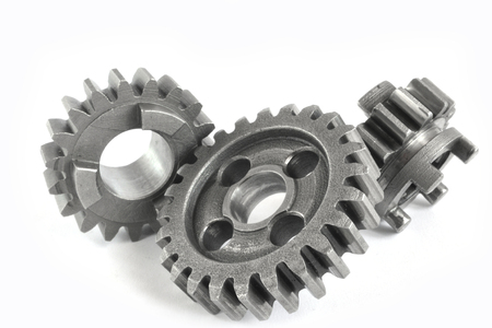 Three close-up metal gears on the white background. Imagens