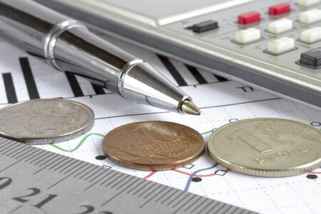 Business background with pen, calculator, coins and graph.