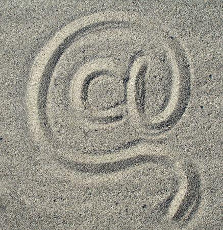manually: Manually at sign on sand