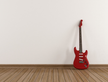 Red electric guitar leaning against a white wall in an empty room