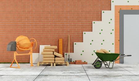 Строительная площадка с бетономешалка, тачка, мешков цемента и панелей для утепления фасада - оказание Фото со стока