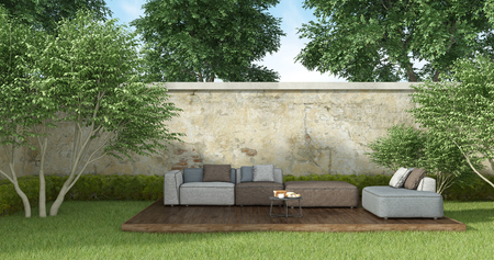 Modern sofa with coffee table in a sunny garden - 3d rendering Stock Photo