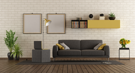 Modern living room with gray sofa,laptop on footstool and brick wall - 3d rendering