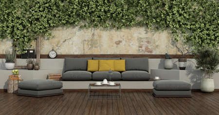 Garden with ivy on old wall and gray sofa, yellow cushion, footstool on wooden flooring - 3d rendering