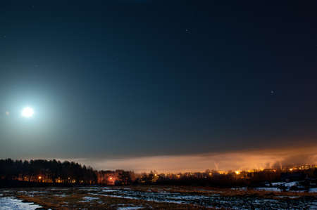 Moon with clouds in the night sky. Cold winter in Lithuania 免版税图像