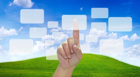 hand pushing on a touch screen in blue sky photo