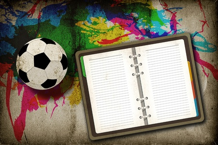 Football and blank notebook on vintage background photo
