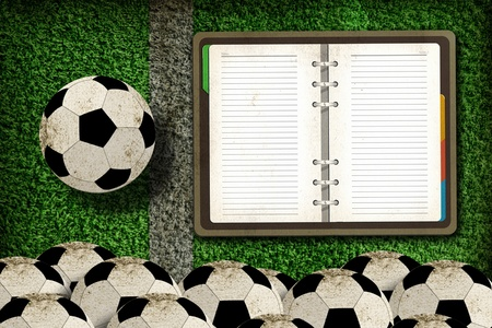 Football and blank notebook on Green Grass background photo
