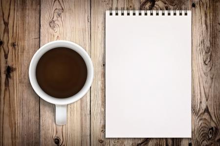 Schetsboek met koffiekopje op houten achtergrond