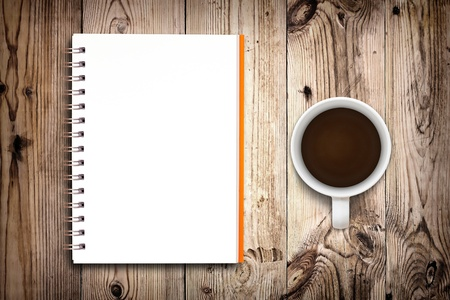 Notebook and coffee cup isolated on wooden background photo