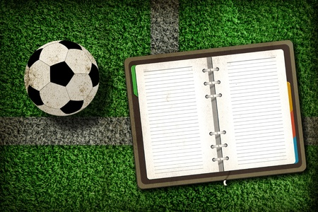 Football and blank notebook on Green Grass background