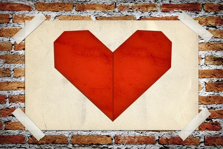 Red heart in old paper stick on brick wall photo
