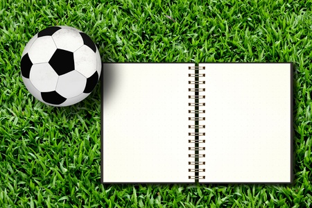 Football and blank notebook on Green Grass photo